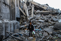 March 26, 2019 - Gaza City, Gaza Strip, Palestinian Territory - Palestinians look at the rubble of what was their homes before the Israeli bombardments of the previous day. Israeli warplanes carried out dozens of airstrikes across the southern, central, and northern Gaza Strip after a Gaza rocket struck an Israeli house north of Tel Aviv, in central Israel, injuring seven Israelis. Israeli warplanes targeted Hamas sites, as well as dozens of residential and commercial buildings, and according to the Palestinian Ministry of Health in Gaza, seven Palestinians suffered various injuries due to the airstrikes (Credit Image: © Ahmad Hasaballah/IMAGESLIVE via ZUMA Wire)