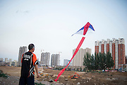 A Chinese man plays with his kite in a construction site in Datong, China, July 24, 2014.<br /> <br /> Food and games are a real pleasure for the life of Chinese community. <br /> At home, in the streets, at the park or in restaurants, the chance to find someone eating or playing is considerably high.<br /> <br /> © Giorgio Perottino
