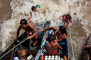 Indiegnous Amazonian children playing in the water next to their boat and selling palm hearts and Acai on the Xingu river in the Amazon region of Para State