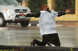 South Africa - Cape Town - 25 May 2020 - A homeless man falls to his knees in the rain whiles begging at a traffic light in Sea Point. Cape Town is in for a rainy week, with two more days of showers on the cards starting from Tuesday. Chilly weather is also on the forecast so residents are cautioned to stay cosy. While Monday has proven to be a windy, rainy and somewhat stormy day, Tuesday, May 26 promises scattered showers and even lower temperatures. Photographer: Armand Hough/African News Agency(ANA)