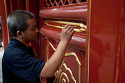 "Man repainting the outside of one of the main temple buildings with gold and earth red paint at Yonghe Temple, also known as the ""Palace of Peace and Harmony Lama Temple"", the ""Yonghe Lamasery"", or - popularly - the ""Lama Temple"" is a temple and monastery of the Geluk School of Tibetan Buddhism located in the northeastern part of Beijing, China. It is one of the largest and most important Tibetan Buddhist monasteries in the world. The building and the artworks of the temple is a combination of Han Chinese and Tibetan styles."