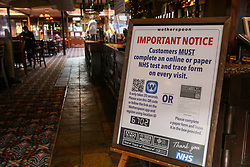 © Licensed to London News Pictures. 26/10/2020. London, UK. A customer notice in a Wetherspoons pub in north London. The hospitality industry estimates that pubs, bars and restaurants have spent £900million on screens, masks and hand sanitisers to make their venues safe for reopening, following the easing of COVID-19 lockdown restrictions. It has been reported that each pub has spent more than £10,000 adapting the interiors of their venues but with the latest restrictions, many now only serve customers outside their premises. Wetherspoons has spent £13.1million on getting its 875 pubs ready. Photo credit: Dinendra Haria/LNP