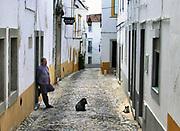 Portugal, Evora, 5-9-2014Oudere man staat in deuropening van een huis, pension . Hond en kat liggen op de straat. Appartementen, pension, slapen, toerisme. prijzen, vakantie, prijspeil, goedkoop.Foto: Flip Franssen