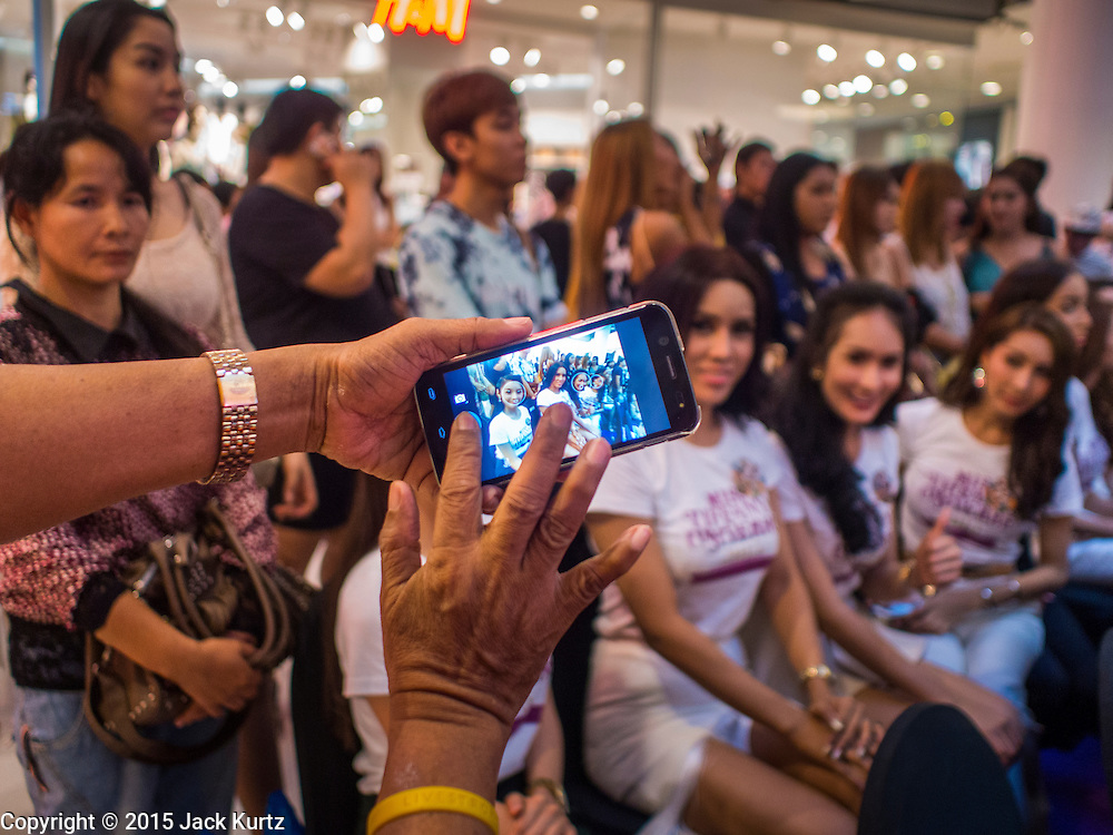 25 MARCH 2015 - BANGKOK, THAILAND: A tourist uses a smart phone to photograph contestants in the first round of the Miss Tiffany's contest at CentralWorld, a large shopping mall in Bangkok. Miss Tiffany's Universe is a beauty contest for transgender contestants; all of the contestants were born biologically male. The final round will be held on May 8 in the beach resort of Pattaya. The final round is televised of the  Miss Tiffany's Universe contest is broadcast live on Thai television with an average of 15 million viewers.     PHOTO BY JACK KURTZ