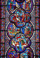 Medieval stained glass Window of the Gothic Cathedral of Chartres, France - dedicated to St John The Evangelist. Bottom left - Armourers making shields and saddles, above right - Armourers making stirrups. Central bottom panel - Death of Satheus, above left - John's journey into exile on Patmos, above right - St John on Patmos. Central top panel - St John confronting Aristodemus, above left and right - The raising of Drusiana . A UNESCO World Heritage Site.. .<br /> <br /> Visit our MEDIEVAL ART PHOTO COLLECTIONS for more   photos  to download or buy as prints https://funkystock.photoshelter.com/gallery-collection/Medieval-Middle-Ages-Art-Artefacts-Antiquities-Pictures-Images-of/C0000YpKXiAHnG2k