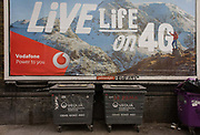Vodafone mountains ad for 4G network services and dystopian refuse bins in south London. While a mountaineer stands on his a personal summit of achievement, amid the adventure of utopian snowy peaks and the great outdoors compared to the reality of the inner-city, an urban ghetto environment of the Elephant & Castle in south London where the streets are filthy and the bins by Veolia Environmental Services have graffiti on them.