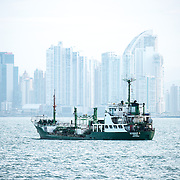 Ships at anchor in Panama Bay waiting their scheduled turn to transit the Panama Canal. The buildings in the distance are on Punta Paitilla in Panama City, Panama.