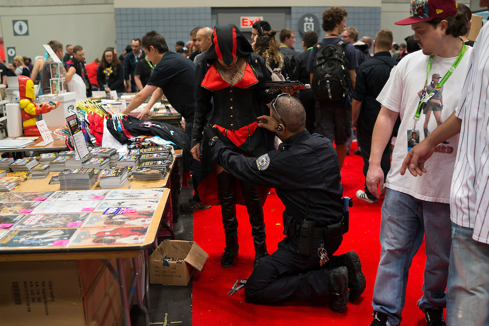 Adaina Velez, center, gets help with her costume from her boyfriend / handler Frank Alvesio, at Comic Con at the Javits Center in New York, NY, on Friday, Oct. 9, 2015. <br /> <br /> Photograph by Andrew Hinderaker