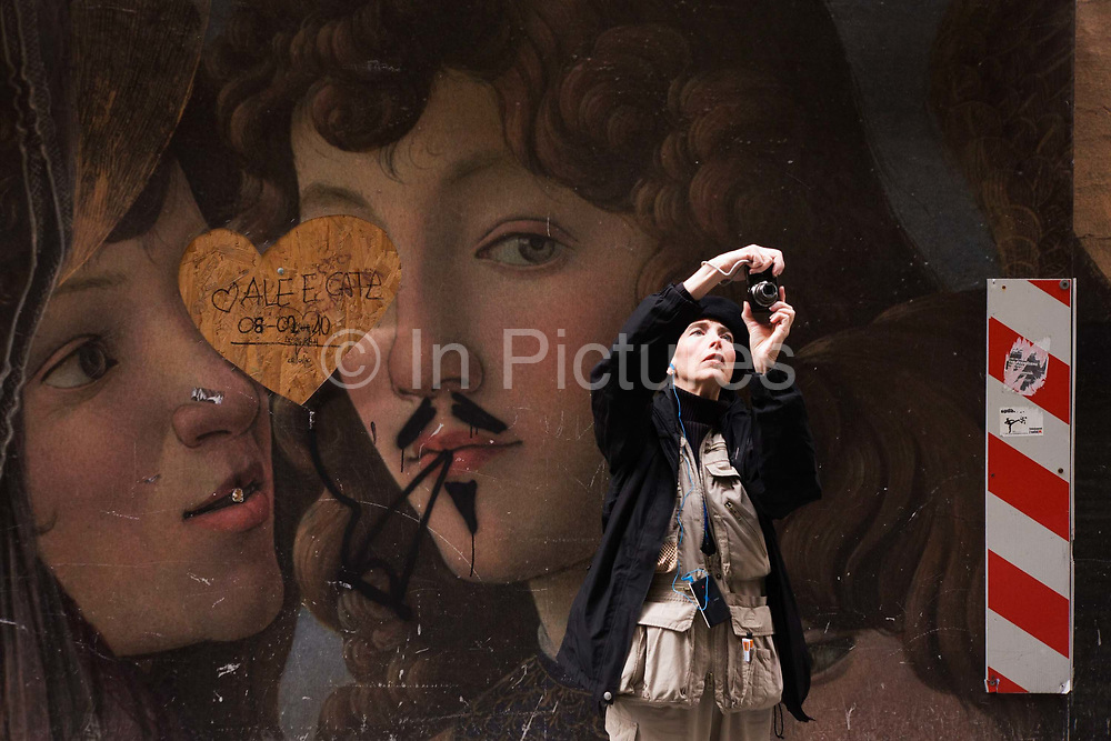 A tourists takes a photo in front of defaced renaissance paintings in Florence's Piazza degli Uffizi. behind her is the reproduction of a renaissance painting that now adorns a construction hoarding screen. Someone has drawn a moustache and cannabis joint in the mouth of a religious character.