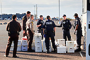 28 JANUARY 2010 -- BUCKEYE, AZ: Arizona Department of Corrections officers and ICE officers load undocumented immigrant inmates' personal effects into an ICE bus. The Arizona Department of Corrections transferred 51 undocumented immigrant inmates from state control to the Immigration and Customs Enforcement at Lewis Prison in Buckeye Thursday morning. The inmates have less than 90 days left on their sentences and will be deported to their countries of origin when they finish their prison terms.   PHOTO BY JACK KURTZ