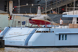 © Licensed to London News Pictures. 16/09/2019. London, UK. A person on board looks at luxury superyacht Ocean Dreamwalker III which is moored next to HMS Belfast on the River Thames, seen with a helicopter on the helipad at the stern of the yacht during a London visit. 155 feet long long Ocean Dreamwalker III was built in 2018 and is rumoured to be owned by John Deng, a Chinese entrepreneur and politician. It is believed that this is the first time a superyacht has visited the capital with a helicopter onboard. Photo credit: Vickie Flores/LNP