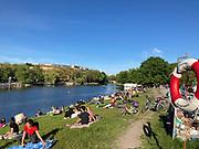 People sit on the bank of the Landwehr Canal (Landwehrkanal) at Kreuzberg district in Berlin, Germany, June 09, 2021.