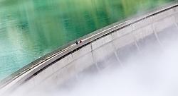 THEMENBILD - Hochgebirgsstauseen Kaprun. Sie dienen der Verbund AG zur Wasserspeicherung für die Stromerzeugung des Kraftwerks Kaprun und sind ein beliebtes Ausflugsziel fuer zahlreiche Touristen, die Mittels Busse und einem Schraegaufzug auf ueber 2000 Meter befoerdert werden. Der Spatenstich erfolgte 1939, ausgefuehrt von Hermann Goering. Seit 1999 gehoert es zur Verbund Hydro Power AG, dem Tochterunternehmen für Wasserkrafterzeugung der Verbund AG, im Bild Touristen spatieren auf der Staumauer des Mooserboden Speichers im Nebel. Bild aufgenommen am 30.09.2012. EXPA Pictures © 2012, PhotoCredit: EXPA/ Juergen Feichter