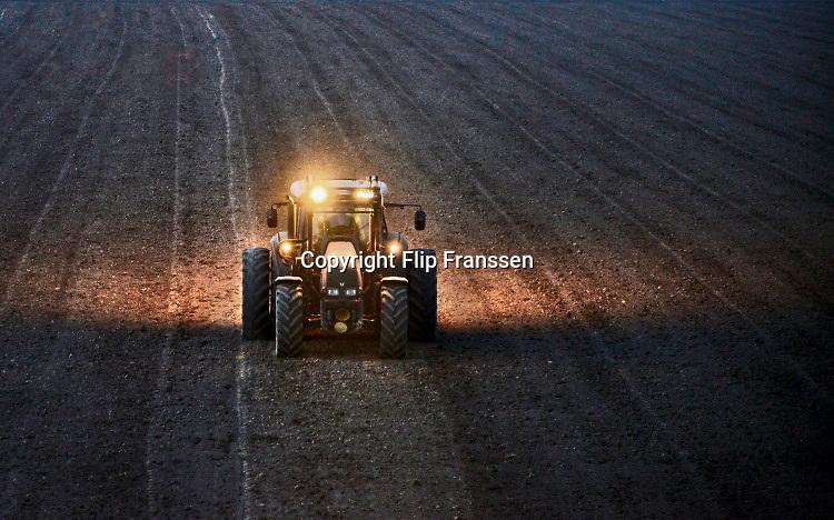 Nederland, Pannerden, 1-4-2020 Boer is tot diep in de avond bezig met zijn trekker de grond te bewerken. Foto: Flip Franssen