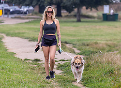 Licensed to London News Pictures. 04/09/202. London, UK. A dog walker on Wimbledon Common, south-west London enjoys the mild weather as weather forecaster predict a mini-heatwave for September. From tomorrow, Sunday, temperatures are expected to hit over 28c for London and the South East. Photo credit: Alex Lentati/LNP