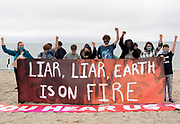 """Climate strikers come together on Gyllyngvase beach as the G7 begins in Cornwall the same weekend. the strikers stand with raised fists behind a banner that reads """"Liar Liar earth is on fire"""" 11th June 2021. Anna Hatfield/Pathos"""
