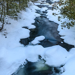The Hudson River in winter as it flows out of Henderson Lake in New York's Adirondack Mountains. Tahawus Tract, Newcomb, New York.