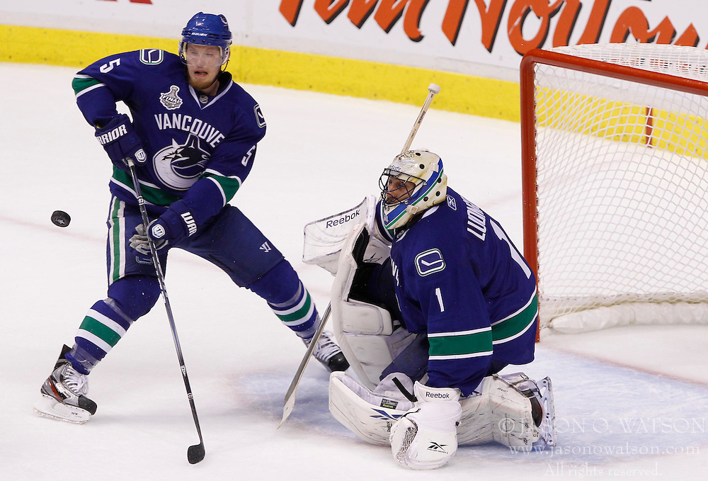 June 10, 2011; Vancouver, BC, CANADA; Vancouver Canucks goalie Roberto Luongo (1) and defenseman Christian Ehrhoff (5) clear the puck in the first period of game five of the 2011 Stanley Cup Finals against the Boston Bruins at Rogers Arena. Mandatory Credit: Jason O. Watson / US PRESSWIRE