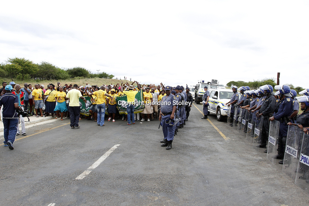 DURBAN - 11 January 2014 - African National Congress supporters march past a house that EFF leader Julius Malema was due to hand over to a grandmother looking after four children. Riot police on the right block access to the house. Picture: Allied Picture Press/APP