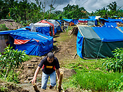 29 JANUARY 2018 - SANTO DOMINGO, ALBAY, PHILIPPINES: A man leaves an impromptu camp in Santo Domingo for people evacuated from their homes because of the Mayon volcano. Many of the shelters in Santo Domingo are filled beyond capacity and people are sleeping tents and huts along the roads.  Mayon volcano's eruptions continued Monday. At last count, more 80,000 people have been evacuated from their homes of the slopes of the volcano and are crowded into shelters in communities outside of the danger zone.    PHOTO BY JACK KURTZ
