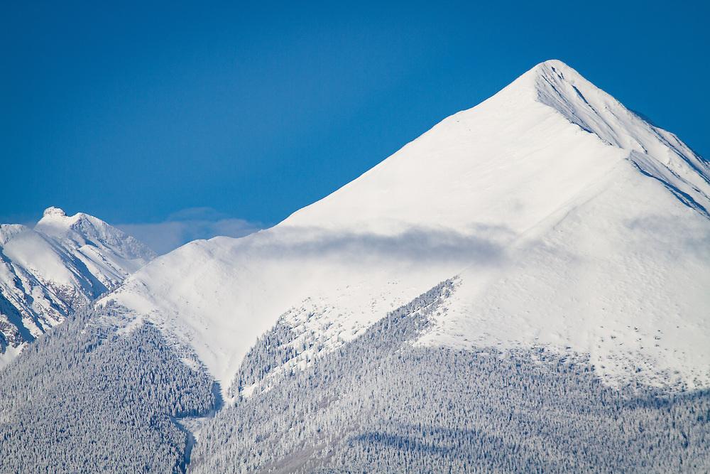Clouds hug the springtime snow-clad peaks of the Sangre de Cristo mountains.
