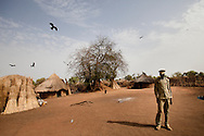 James Kumen a young district administrator stands in the compound where he sleeps near Boma in Jonglei state South Sudan. Armed only with a creditless satellite phone and a university educaction he is responsible for administering dozens of remote hamlets and villages.