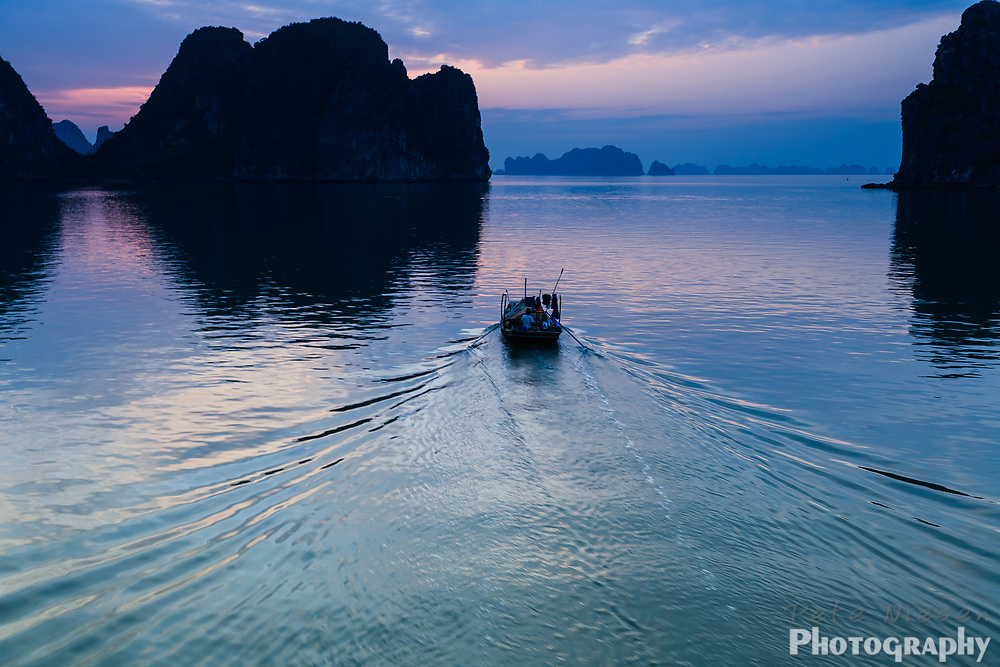 Boat creats a ripple wake as it motors through the blue and pink light on the water at twilight on Halong Bay