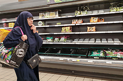 © Licensed to London News Pictures. 31/07/2021. London, UK. A shopper walks past nearly-empty shelves of vegetables in Sainsbury's, north London. Record breaking numbers of people have been forced to self-isolate after being alerted by the NHS Covid-19 app. The pingdemic has seen staff shortages at supermarkets, resulting in less stock making its way to supermarket shelves. Labour leader Sir Keir Starmer has demanded that the government brings forward the end to self-isolation from 16 August to 7 August. Photo credit: Dinendra Haria/LNP
