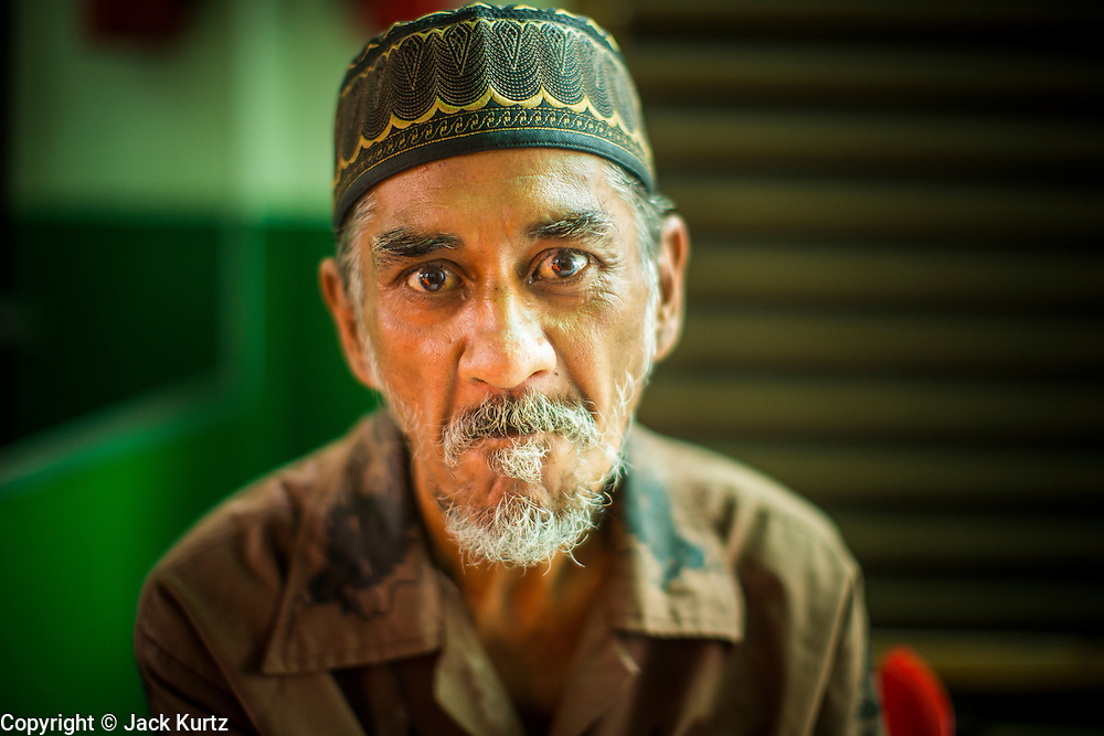 "11 JANUARY 2013 - BANGKOK, THAILAND:    A Muslim man in the Ban Krua neighborhood in Bangkok. The Ban Krua neighborhood of Bangkok is the oldest Muslim community in Bangkok. Ban Krua was originally settled by Cham Muslims from Cambodia and Vietnam who fought on the side of the Thai King Rama I. They were given a royal grant of land east of what was then the Thai capitol at the end of the 18th century in return for their military service. The Cham Muslims were originally weavers and what is known as ""Thai Silk"" was developed by the people in Ban Krua. Several families in the neighborhood still weave in their homes.                PHOTO BY JACK KURTZ"
