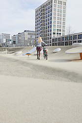Teenage girl walking with bicycle in a playground, Munich, Bavaria, Germany