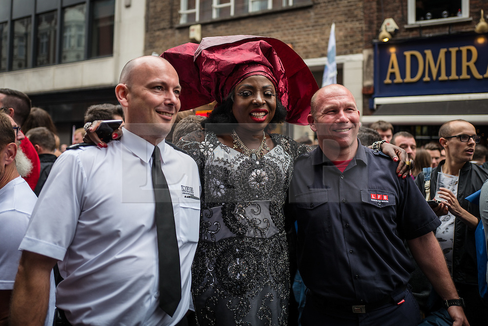 © Licensed to London News Pictures. 13/06/2016. London, UK. A drag queen stands with two firefighters on Old Compton Street in Soho for a vigil to pay tribute to the victims of the Pulse nightclub massacre in Orlando, Florida. In the early hours of 12 June 2016, 29-year-old Omar Mateen entered Pulse, a gay nightclub, and killed more than 50 people with an assault rifle, making it the deadliest mass shooting in US history. Photo credit: Rob Pinney/LNP