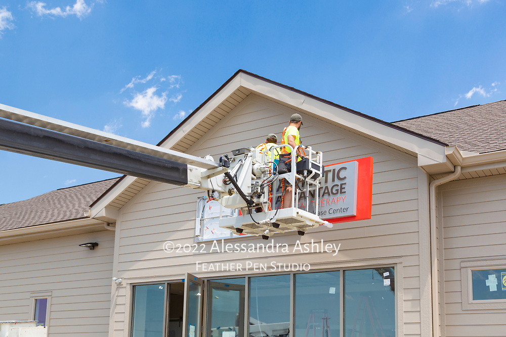 Building sign installation in progress at site of new physical therapy and wellness center.