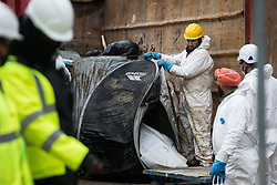 London, UK. 6th February, 2021. HS2 workers wearing white body suits remove a tent used by environmental activists from anti-HS2 campaign group HS2 Rebellion from Euston Square Gardens. National Eviction Team bailiffs have been working for the past eleven days to remove activists from tunnels dug by them beneath the site in order to seek to protect trees from felling in connection with the HS2 high-speed rail project.