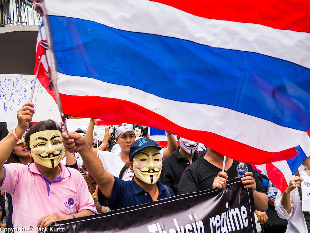 """02 JUNE 2013 - BANGKOK, THAILAND: Anti-government protesters march through Bangkok waving a Thai flag. The so called White Mask protesters are strong supporters of the Thai monarchy. About 300 people wearing the Guy Fawkes mask popularized by the movie """"V for Vendetta"""" and Anonymous, the hackers' group, marched through central Bangkok Sunday demanding the resignation of Prime Minister Yingluck Shinawatra. They claim that Yingluck is acting as a puppet for her brother, former Prime Minister Thaksin Shinawatra, who was deposed by a military coup in 2006 and now lives in exile in Dubai.     PHOTO BY JACK KURTZ"""