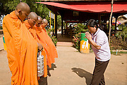 """26 JUNE 2006 - CENTRAL CAMBODIA: A woman gives """"alms"""" to a group of Buddhist monks during a stop on Highway 6 between Phnom Penh and Siem Reap, Cambodia. PHOTO BY JACK KURTZ"""