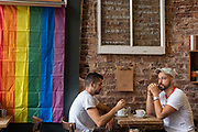 Two men sitting in a coffee shop on the day of the Brighton Pride parade on the 3rd August 2019 in Brighton in the United Kingdom.
