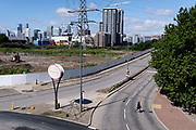 With the high-rise wealth of London Docklands in the distance, a female pedestrian crosses a quiet dual-carriageway at Canning Town in Newham, on 11th August 2021, in London, England.