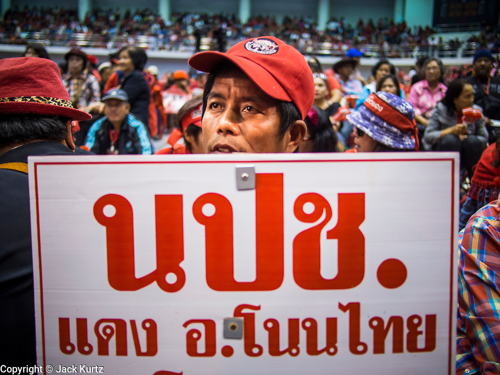 """23 FEBRUARY 2014 - NAKHON RATCHASIMA (KORAT), NAKHON RATCHASIMA, THAILAND: A Red Shirt supporter at the Red Shirt meeting in Korat. The United front of Democracy against Dictator (UDD or Red Shirts), which supports the elected government of Yingluck Shinawatra, staged the """"UDD's Sounding of the Battle Drums"""" rally in Nakhon Ratchasima (Korat) to counter the anti-government protests that have gripped Bangkok since November. Around 4,000 of UDD's regional and provincial coordinators along with the organization's core members met at Liptapunlop Hall inside His Majesty the King's 80th Birthday Anniversary Sports Complex in Korat to discuss the organization's objectives and tactics against anti-government protestors, which the UDD says """"seek to destroy the country's democracy."""" The UDD leadersa announced that they will march to Bangkok and demonstrate against anti-government protests led by Suthep Thaugsuban.   PHOTO BY JACK KURTZ"""