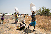 Mcc0075406 . Daily Telegraph<br /> <br /> DT Foreign<br /> <br /> Women take away their bags of Sorghum grain from the food distribution centre .<br /> <br /> Women and children walked for hours today to UN food air drop in Padeah , in a famine hit area of war torn Unity State . <br /> <br /> <br /> Padeah 1 March 2017