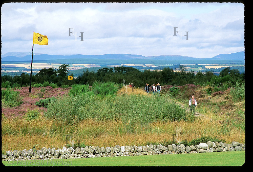 Visitors walk by yellow flags marking Redcoat battle lines at Culloden Moor on April 16, 1746; Inverness, Scotland.