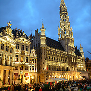 Town Hall in the Grand Place, Brussels, at dusk. Originally the city's central market place, the Grand-Place is now a UNESCO World Heritage site. Ornate buildings line the square, including guildhalls, the Brussels Town Hall, and the Breadhouse, and seven cobbelstone streets feed into it.