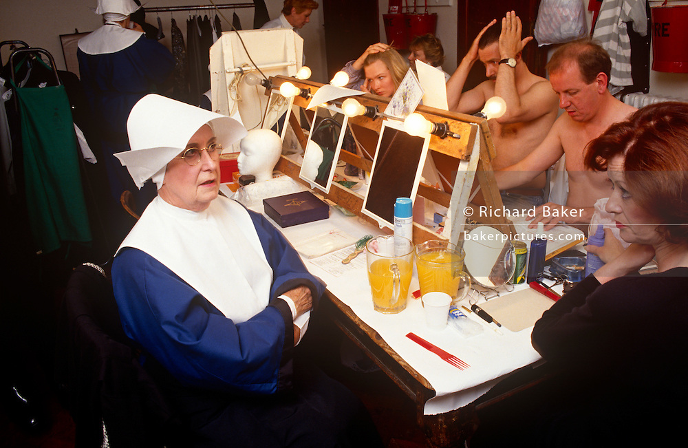 Amateur dramatic actors sit applying make-up and rehearse dialogue before their local production of Bonaventure.
