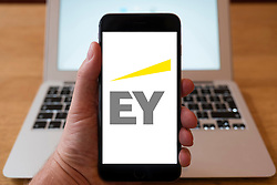Using iPhone smart phone to display website logo of EY (Ernst & Young) a multinational professional services firm