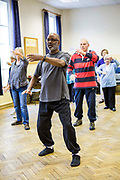 A man leads a Tai Chi class in a community centre for local elderly residents of Bath, Somerset. Tai Chi is a Chinese martial art practised for defence training and health benefits.