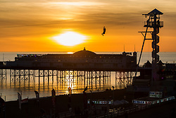 © Licensed to London News Pictures. 30/10/2017. Brighton, UK. Members of the public take a ride on the Brighton Zipwire attraction as the sun sets behind the Brighton Palace pier in Brighton and Hove. Photo credit: Hugo Michiels/LNP