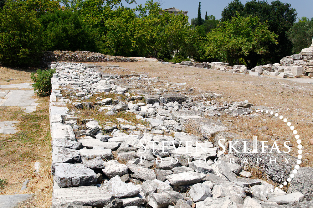 Ancient Agora. Athens. Greece. View from within the slight remains of the Odeion of Agrippa in the central area of the Agora. The Odeion, built by Marcus Vipsanius Agrippa son in law of Emperor Augustus in 15 BC, was a roofed building, with a two-storeyed portico, a semicircular orchestra and could accommodate 1000 spectators. It was destroyed by the Herulians in 267 AD.  In 400 AD, the Palatial Palace was built over the remains of the Odeion of Agrippa, the Palace was a large complex consisting of courtyards, gardens, baths and numerous rooms.