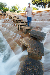 Man on steps of the Active Pool at Fort Worth Water Gardens, Fort Worth, Texas, USA.
