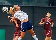A Notre Dame women's soccer player advances the ball against a Minnesota defender.