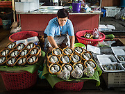 27 SEPTEMBER 2016 - BANGKOK, THAILAND: A vendor sets up her booth selling fish and seafood in the market in the Samut Songkhram train station. The train from Baen Laem to Samut Songkhram (Mae Khlong) recently resumed service. The 33 kilometer track was closed for repair for almost a year. In Samut Songkhram, the train passes over the market. Vendors pull their stands out of the way and people step out of the way as the train passes through the market. It is one of the most famous train stations in Thailand and has become an important tourist attraction in the community.     PHOTO BY JACK KURTZ