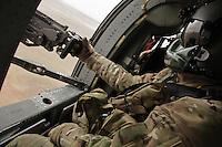 An American army door gunner in a Black Hawk over Kandahar.